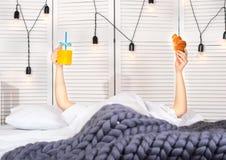 Uma mulher está tendo o café da manhã na cama Suco de laranja e um croissant fotografia de stock royalty free