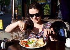 Uma mulher está tendo o café da manhã no terraço em um café Fotografia de Stock Royalty Free
