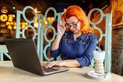 Uma mulher está trabalhando atrás de um portátil em uma tabela em um café, abaixando seus vidros em um fundo borrado Imagens de Stock