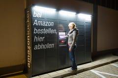 Uma mulher está usando uma estação do cacifo das Amazonas situada ao lado de um supermercado de Aldi imagens de stock