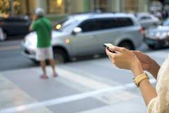 Uma mulher está usando seu telefone imagem de stock