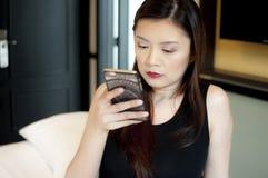 Uma mulher está usando um telefone celular foto de stock royalty free