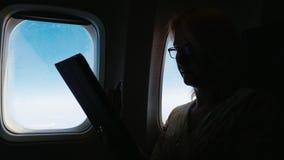 Uma mulher está voando em um avião, lendo algo na tabuleta Silhueta, vista lateral vídeos de arquivo