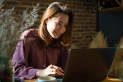 Uma mulher est? comprando no Internet ao p?r pouco sorriso sobre sua cara imagem de stock royalty free