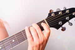 Uma mulher est? jogando uma guitarra ac?stica imagens de stock royalty free