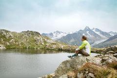 Uma mulher está sentando-se na rocha no lago da montanha Fotografia de Stock