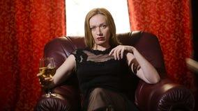 Uma mulher fatal em um vestido preto e em um batom vermelho em seus bordos senta-se em uma cadeira de couro com um vidro do vinho vídeos de arquivo
