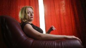 Uma mulher fatal em um vestido preto e em um batom vermelho em seus bordos senta-se em uma cadeira de couro e olha-se arroganteme video estoque