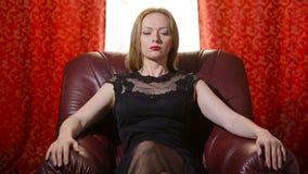 Uma mulher fatal em um vestido preto e em um batom vermelho em seus bordos senta-se em uma cadeira de couro e olha-se arroganteme filme