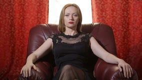 Uma mulher fatal em um vestido preto e em um batom vermelho em seus bordos senta-se em uma cadeira de couro e olha-se arroganteme vídeos de arquivo