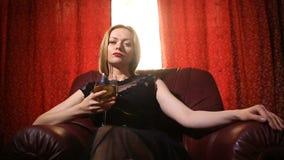 Uma mulher fatal em um vestido preto e em um batom vermelho em seus bordos senta-se em uma poltrona de couro com um vidro do vinh filme