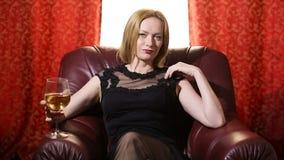 Uma mulher fatal em um vestido preto e em um batom vermelho em seus bordos senta-se em uma poltrona de couro com um vidro do vinh vídeos de arquivo