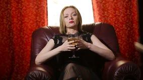 Uma mulher fatal em um vestido preto e em um batom vermelho em seus bordos senta-se em uma poltrona de couro com um vidro do vinh video estoque