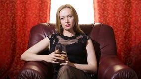 Uma mulher fatal em um vestido preto e em um batom vermelho em seus bordos senta-se em uma poltrona de couro e olha-se arrogantem video estoque