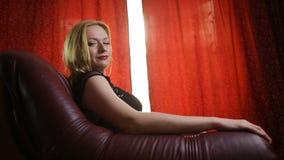 Uma mulher fatal em um vestido preto e em um batom vermelho em seus bordos senta-se em uma poltrona de couro e olha-se arrogantem vídeos de arquivo