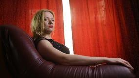 Uma mulher fatal em um vestido preto e em um batom vermelho em seus bordos senta-se em uma poltrona de couro e olha-se arrogantem filme