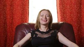 Uma mulher fatal em um vestido preto e em um batom vermelho em seus bordos senta-se em uma poltrona de couro, olha-se na câmera e video estoque