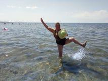 Uma mulher feliz está estando no mar Foto de Stock Royalty Free