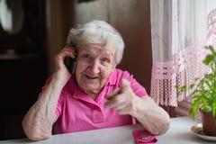 Uma mulher feliz idosa que fala no telefone que senta-se em uma tabela em sua casa imagens de stock