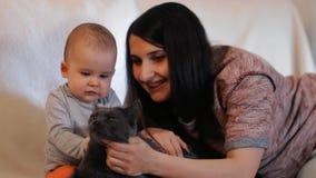 Uma mulher feliz nova mostra a seu filho pequeno como pet um gato filme