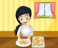 Uma mulher feliz que prepara sanduíches ilustração royalty free