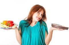 Uma mulher gravida é alimento da terra arrendada imagem de stock