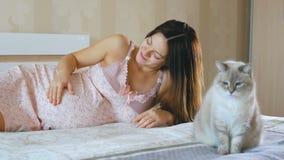 Uma mulher gravida acordou e afagou sua barriga O gato está sentando-se na cama ao lado dela A menina sorri e olha video estoque