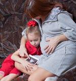 Uma mulher gravida com sua filha Imagens de Stock Royalty Free
