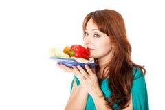 Uma mulher gravida com uma placa dos vegetais imagem de stock