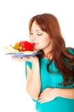 Uma mulher gravida com uma placa dos vegetais imagens de stock