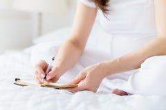 Uma mulher gravida europeia escreve alguns ideia ou thouths no livro de nota pela pena que senta-se na cama branca da sala clara  Foto de Stock Royalty Free