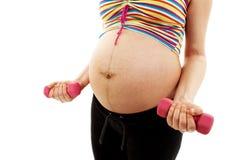 Uma mulher gravida que elabora com pesos Fotografia de Stock