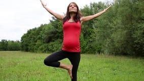 Uma mulher gravida que faz a ioga video estoque