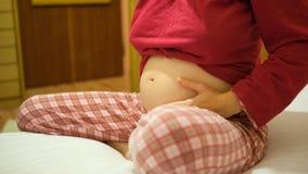 Uma mulher gravida que toca em sua barriga Foto de Stock