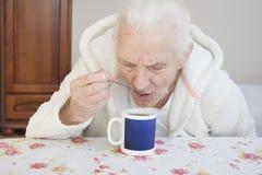 Uma mulher grisalho idosa senta-se em uma tabela e bebe-se o chá de uma colher de chá inclinada sobre uma caneca imagens de stock royalty free