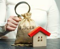 Uma mulher guarda uma lupa sobre um saco do dinheiro com os preços da palavra e uma casa de madeira O conceito da análise de preç fotos de stock royalty free