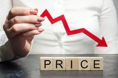 Uma mulher guarda uma seta vermelha para baixo sobre blocos de madeira e o preço da palavra Conceito do valor de mercado de queda imagens de stock