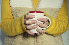 Uma mulher guarda um copo quente do chá e aquece suas mãos Foto de Stock Royalty Free