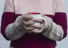 Uma mulher guarda um copo quente do chá e aquece suas mãos Foto de Stock
