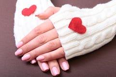 Uma mulher guarda um coração vermelho em suas mãos Imagens de Stock