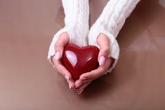 Uma mulher guarda um coração vermelho em suas mãos Imagem de Stock Royalty Free