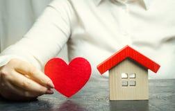 Uma mulher guarda um coração vermelho perto da casa de madeira Serviços do agente de seguros Conceito do seguro patrimonial Prote imagens de stock