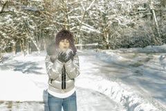 Uma mulher guarda um punhado da neve em suas mãos e funde nele Wi Imagens de Stock