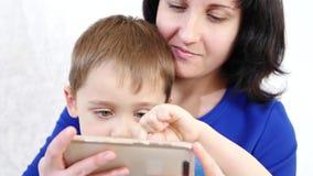 Uma mulher guarda um rapaz pequeno que abraça o A criança toca no tela táctil do telefone e joga um jogo da criança s na video estoque