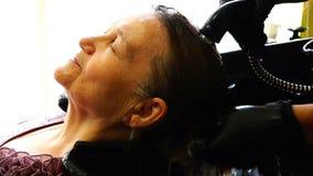 Uma mulher idosa admira a lavagem de sua cabeça em um salão de beleza filme