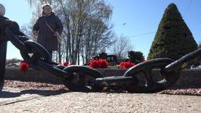 Uma mulher idosa aproxima o monumento em que mentira as flores vídeos de arquivo
