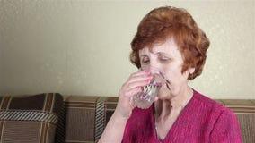 Uma mulher idosa bebe a água de um vidro video estoque