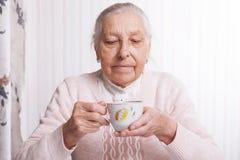 Uma mulher idosa bebe o chá em casa Mulher superior que guarda o copo do chá em suas mãos no close up da tabela fotos de stock