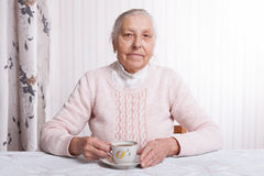 Uma mulher idosa bebe o chá em casa Mulher superior que guarda o copo do chá em suas mãos no close up da tabela imagem de stock