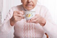 Uma mulher idosa bebe o chá em casa Mulher superior que guarda o copo do chá em suas mãos no close up da tabela imagens de stock royalty free